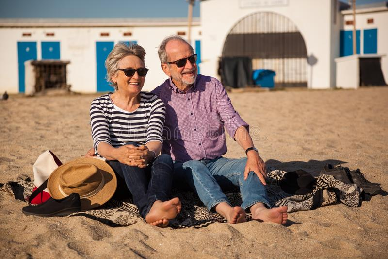Elderly couple sitting on mediterranean beach, concept happy active seniors. A happy senior couple sitting on the beach and enjoying the view end the sunshine stock photo