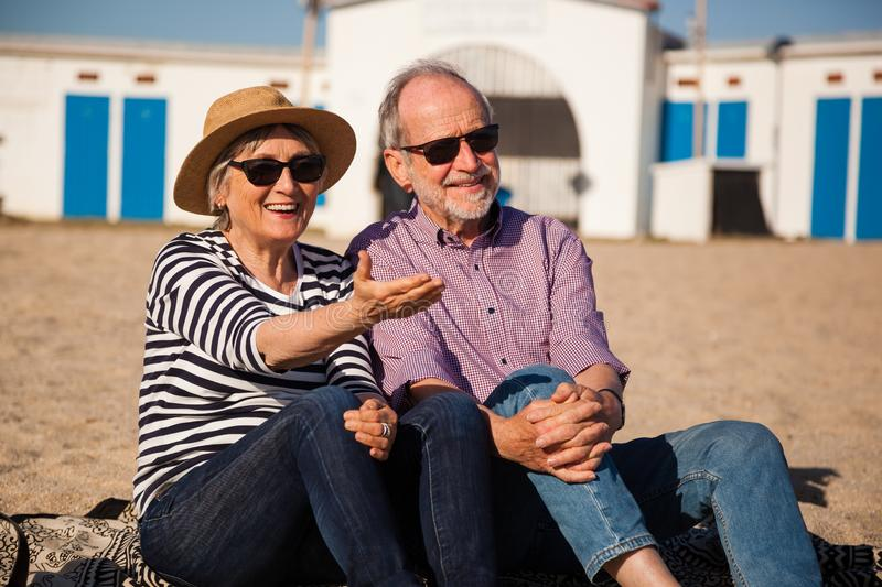 Elderly couple sitting on mediterranean beach, concept happy active seniors. A happy senior couple sitting on the beach and enjoying the view end the sunshine royalty free stock photos