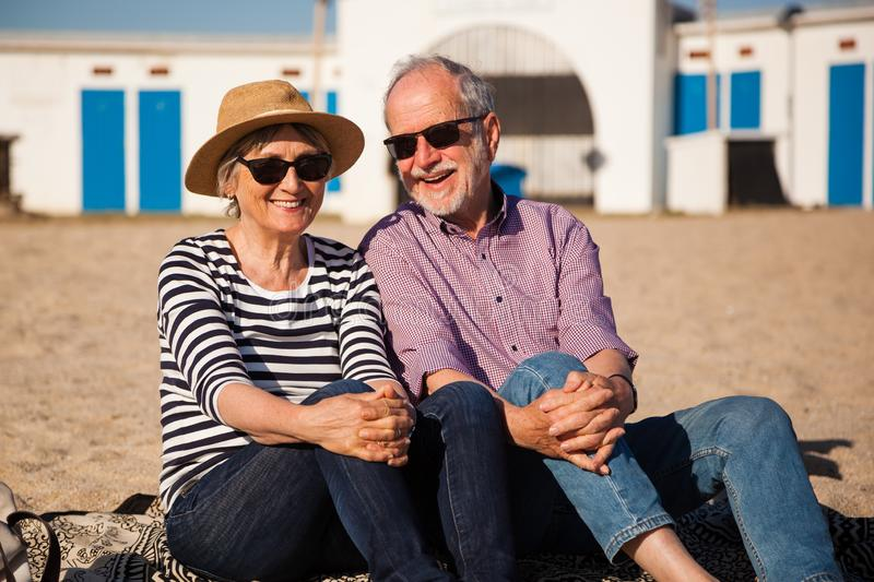 Elderly couple sitting on mediterranean beach, concept happy active seniors. A happy senior couple sitting on the beach and enjoying the view end the sunshine stock image