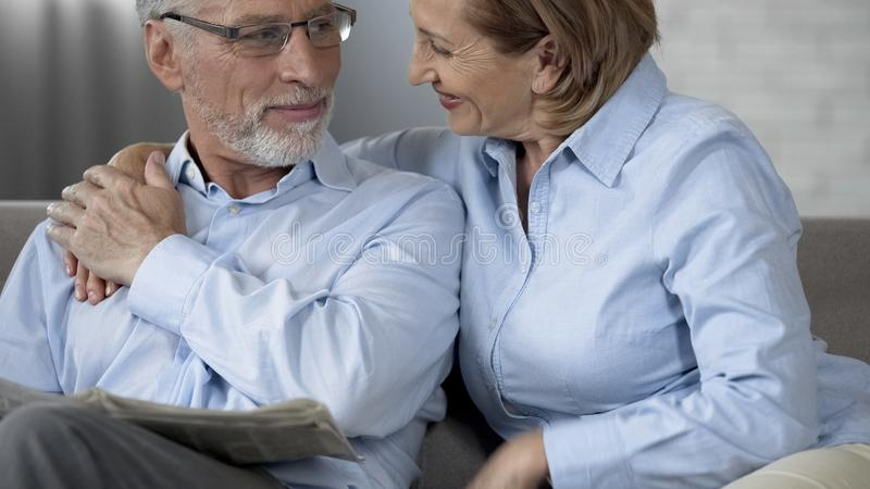 Elderly couple sitting on sofa, looking at each other and smiling, both happy royalty free stock images