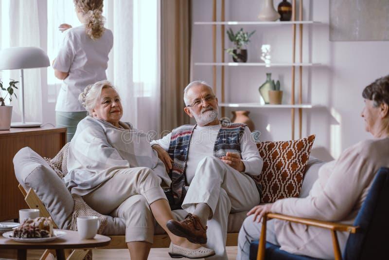Elderly couple sitting on the sofa in the nursing home. Interior stock photo