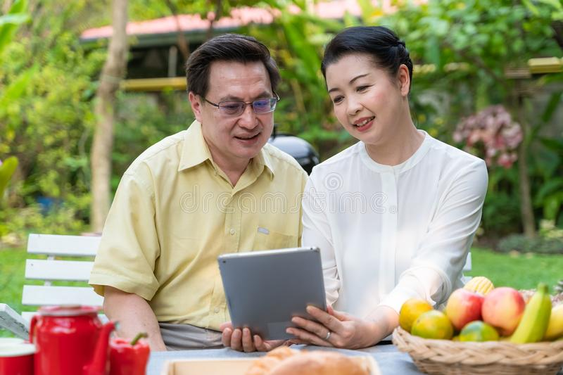 An elderly couple is sitting watching the tablet royalty free stock photos