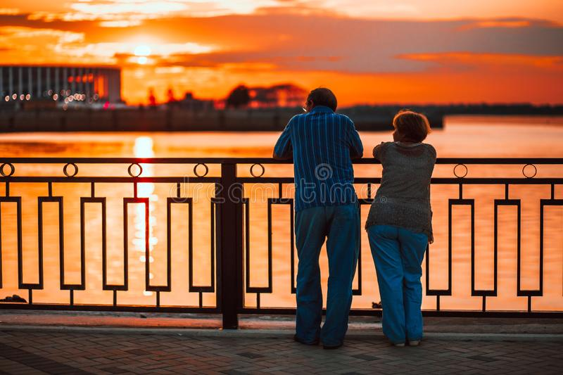 Elderly couple standing back on the river bank and watching the sunset royalty free stock photography