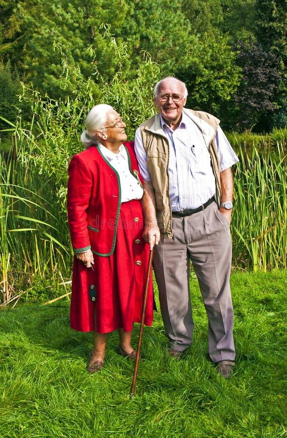 Elderly Couple Standing Hand In Hand In Their Garden Royalty Free Stock Photos