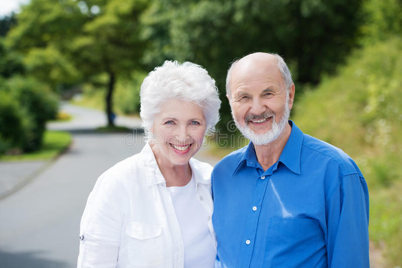 Elderly couple standing in a rural road stock photo