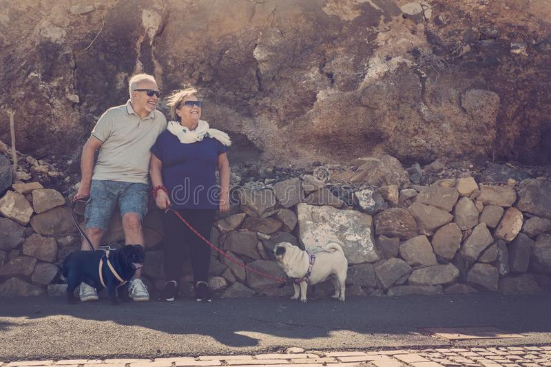Senior man and woman with two pugs look at the sun stock photos