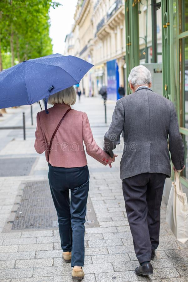 Elderly couple under umbrella holding hands. Loving each other old people go down the street. stock photos