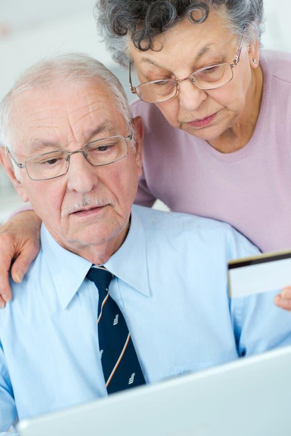Elderly couple using card on internet royalty free stock photos