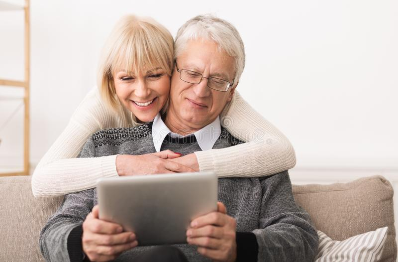 Elderly couple using digital tablet in living room stock image