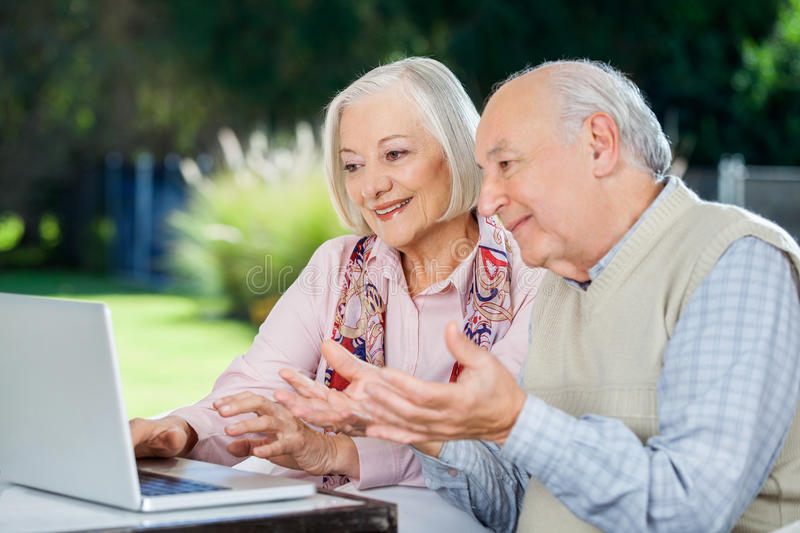 Elderly Couple Video Chatting On Laptop. While sitting at nursing home porch royalty free stock photo