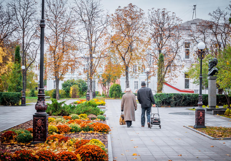 Elderly couple walking in autumn Park royalty free stock images