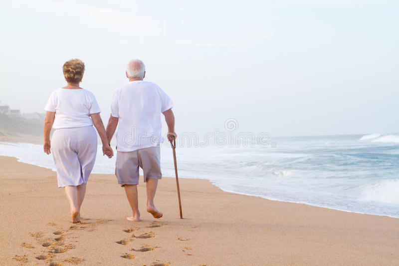 Elderly couple walking on beach royalty free stock image