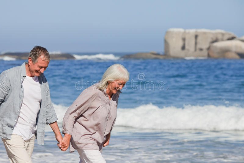 Elderly Couple Walking On The Beach Stock Images