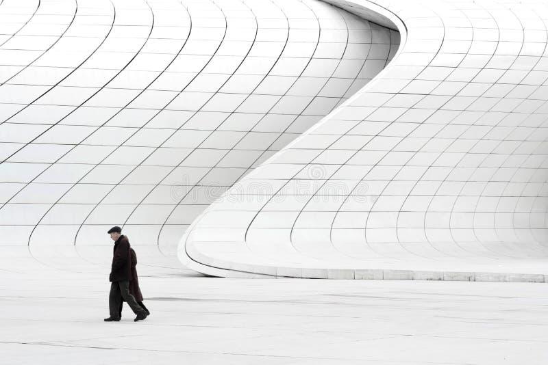 Elderly couple walking near modern buildings stock image
