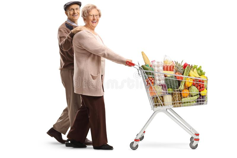 Elderly couple walking and pushing a shopping cart with food products. Full length shot of an elderly couple walking and pushing a shopping cart with food stock photography