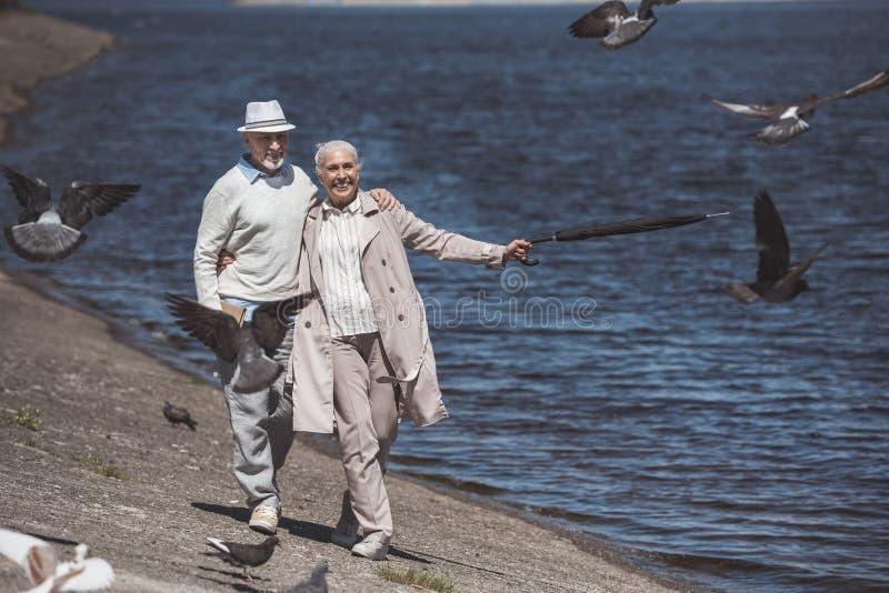 Elderly couple walking on river shore at daytime stock photos