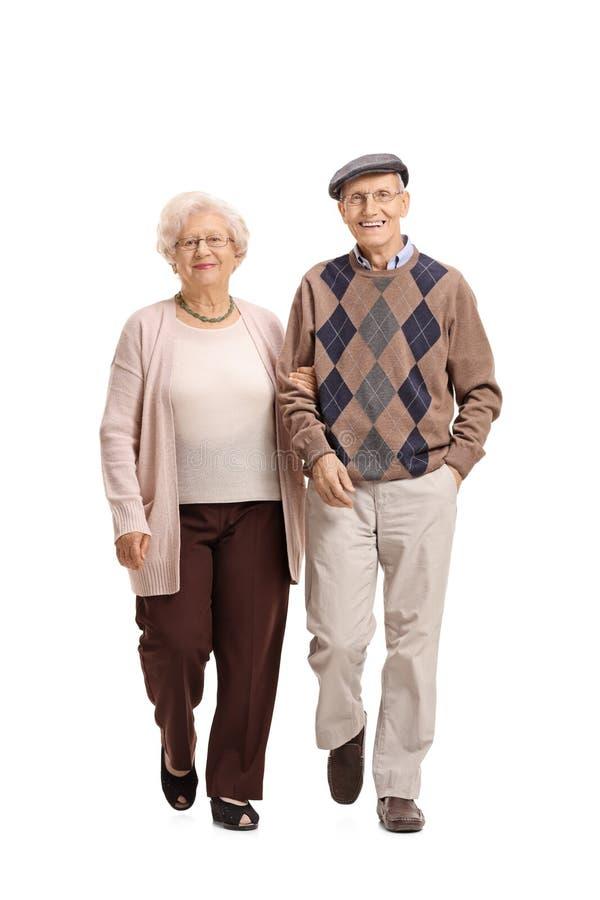 Elderly couple walking towards the camera. Full length portrait of an elderly couple walking towards the camera isolated on white background royalty free stock photography