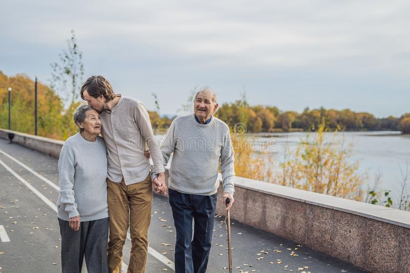An elderly couple walks in the park with a male assistant or adult grandson. Caring for the elderly, volunteering.  stock photo