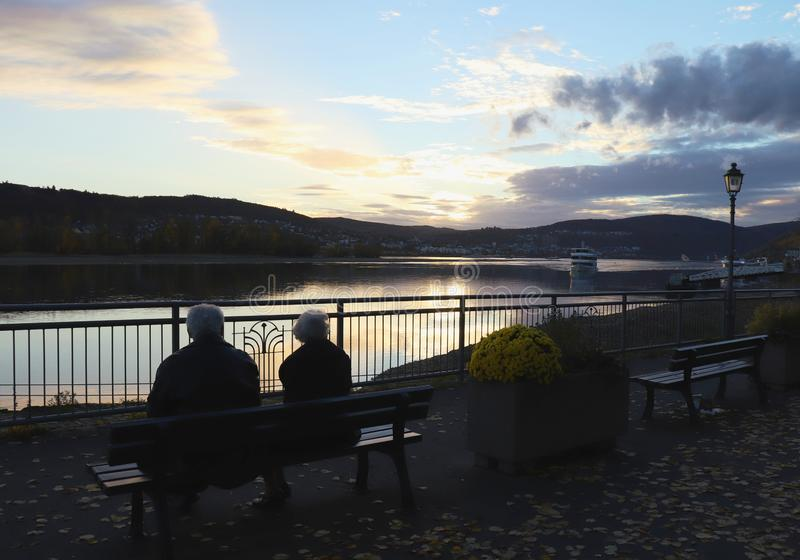 Elderly couple watches sunset on Rhine River. An elderly couple sitting on a bench watching the sunset on the Rhine River in Rudesheim am Rhine, Germany on a royalty free stock photos