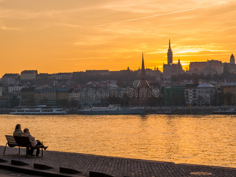 Elderly couple watching sunset. Elderly couple sitting on a bench, watching the sunset over the Danube River in Budapest, Hungary stock photo