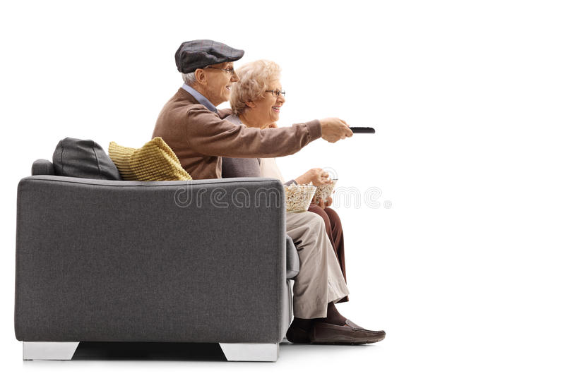 Elderly couple watching television with one of them holding a re. Elderly couple sitting on a couch and watching television with one of them holding a remote stock image