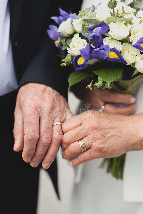 An elderly couple after the wedding in the Church, their hands close-up. Wedding of the elderly, the bride holds a beautiful stock image
