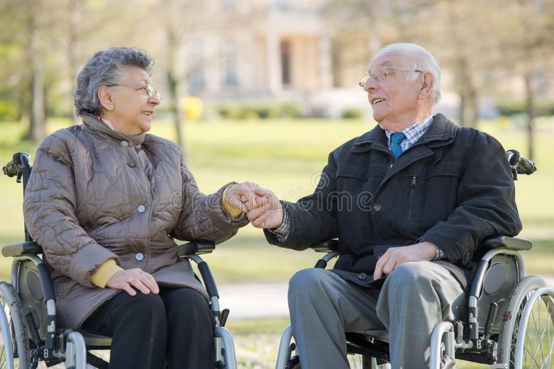 Elderly couple in wheelchairs holding hands. Elderly stock photography