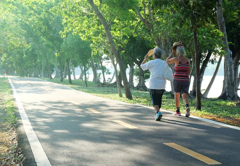 Elderly couple women walking exercise at the park in the afternoon light royalty free stock photography