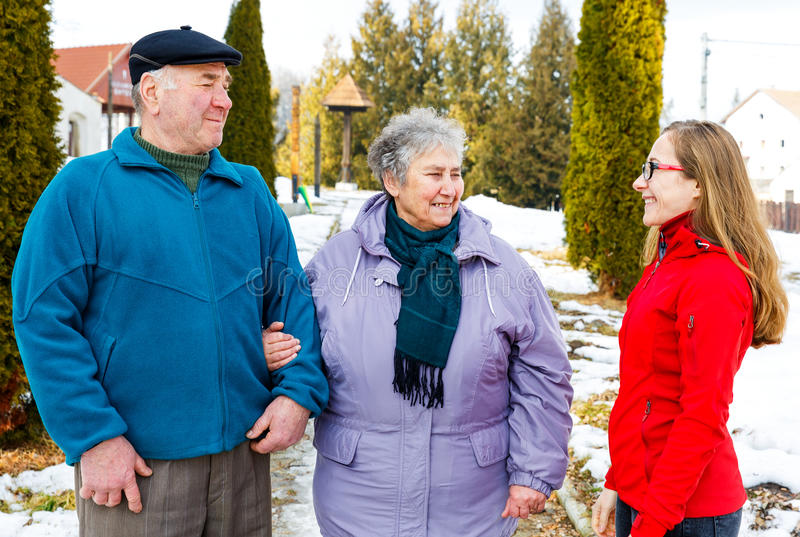 Elderly couple and young caregiver. Walking in the park in wintertime royalty free stock photo