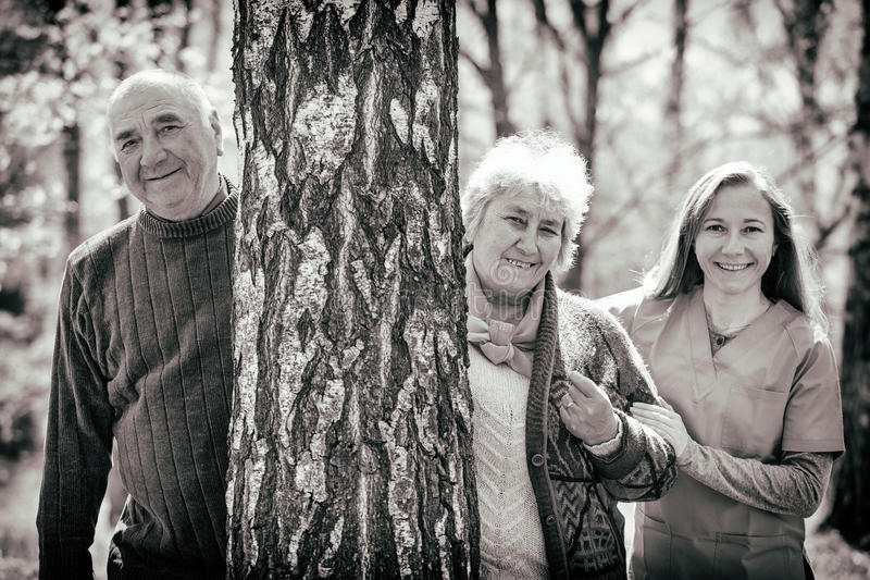 Elderly couple and young caregiver. Having fun together stock image