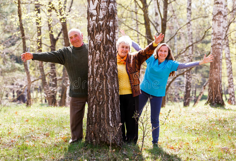 Elderly couple and young caregiver. Having fun together stock images