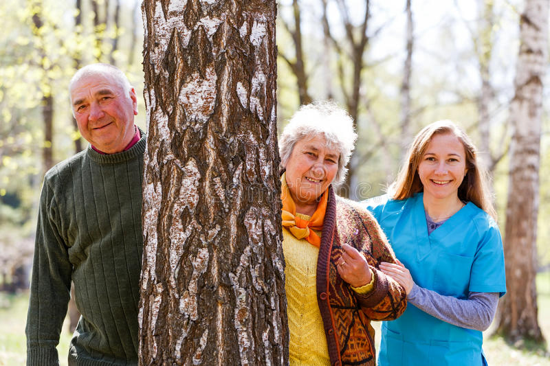 Elderly couple and young caregiver. Having fun together stock photo