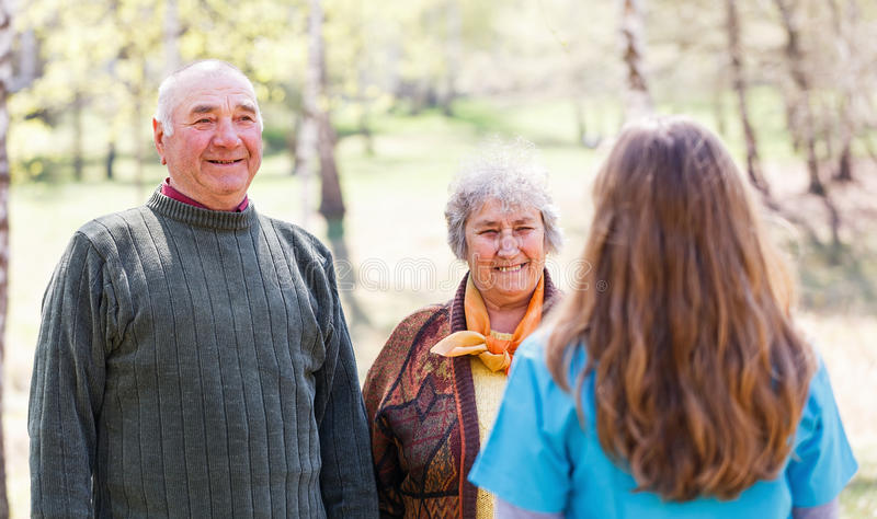 Elderly couple and young caregiver. Photo of elderly couple and young caregiver royalty free stock photos