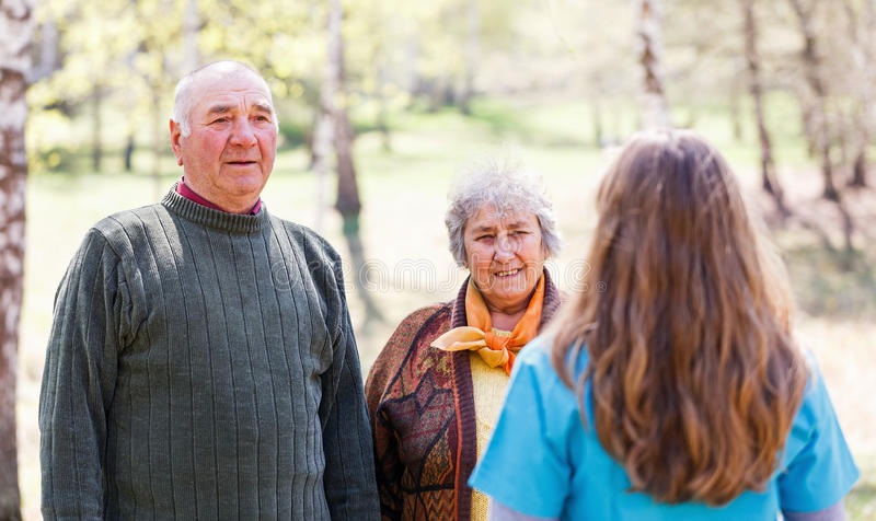 Elderly couple and young caregiver. Photo of elderly couple and young caregiver stock photos