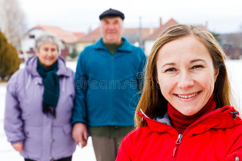 Elderly couple and young caregiver. Photo of happy elderly couple and young caregiver stock photos