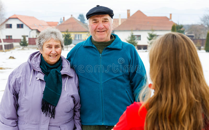 Elderly couple and young caregiver. Photo of happy elderly couple and young caregiver royalty free stock photos