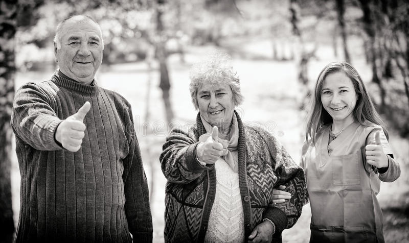 Elderly couple and young caregiver royalty free stock photography