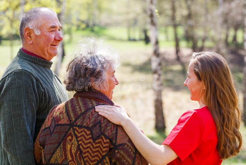 Elderly couple and young caregiver. Photo of elderly couple and young caregiver walking in the nature royalty free stock photos