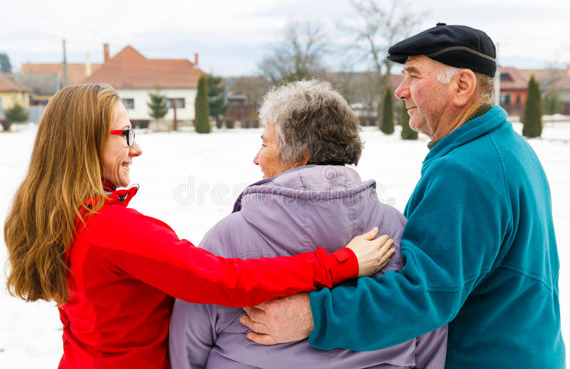 Elderly couple and young caregiver. Walking in the park in wintertime stock photography