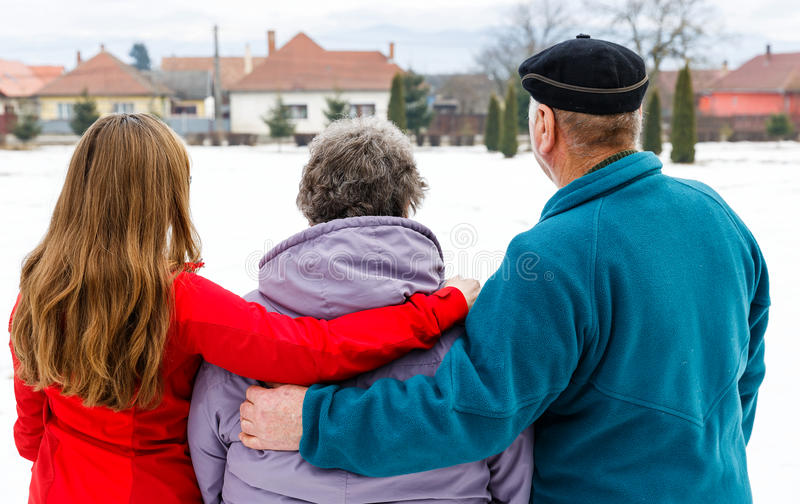 Elderly couple and young caregiver. Walking in the park in wintertime royalty free stock image