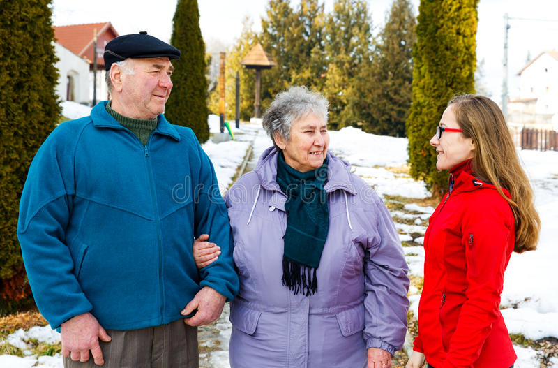 Elderly couple and young caregiver. Walking in the park in wintertime stock images