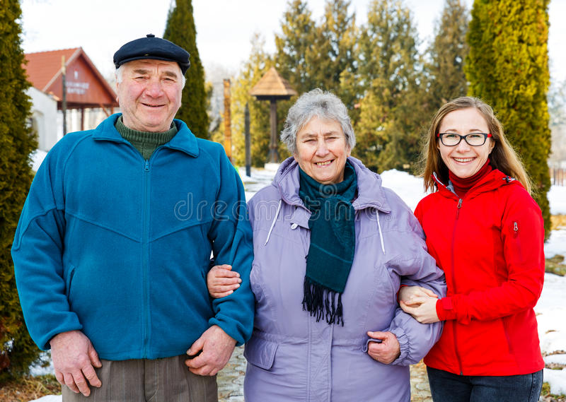 Elderly couple and young caregiver. Walking in the park in wintertime stock photos