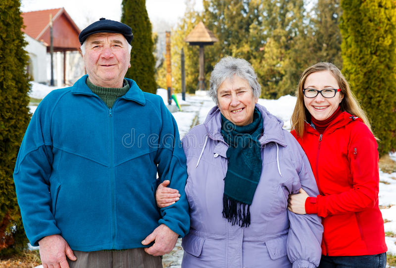 Elderly couple and young caregiver. Walking in the park in wintertime royalty free stock photography