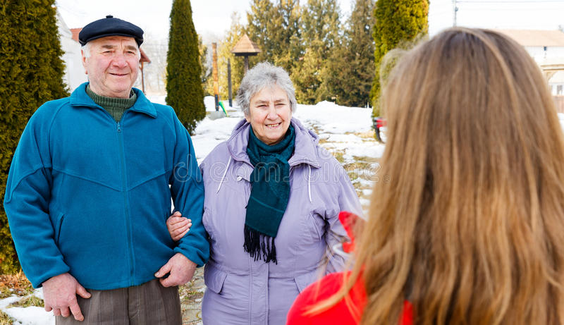 Elderly couple and young caregiver. Walking in the park in wintertime royalty free stock images