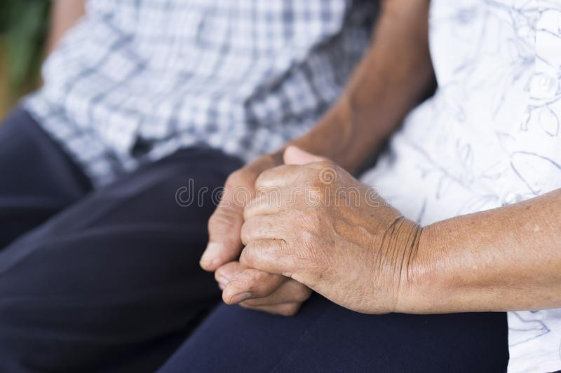 Elderly couples holding older hands and sitting together. Concept of take care together royalty free stock images