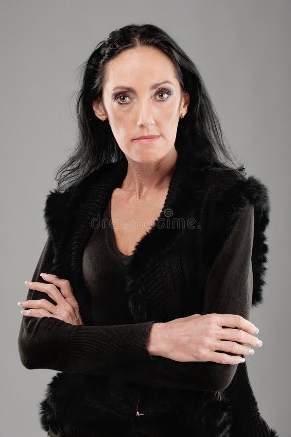 Elderly dark-haired woman. Portrait of beautiful elderly dark-haired woman in black clothes stock image