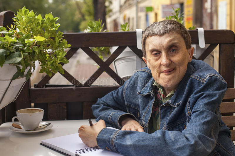 Elderly disabled man with cerebral palsy in outdoor cafe. Portrait. stock image