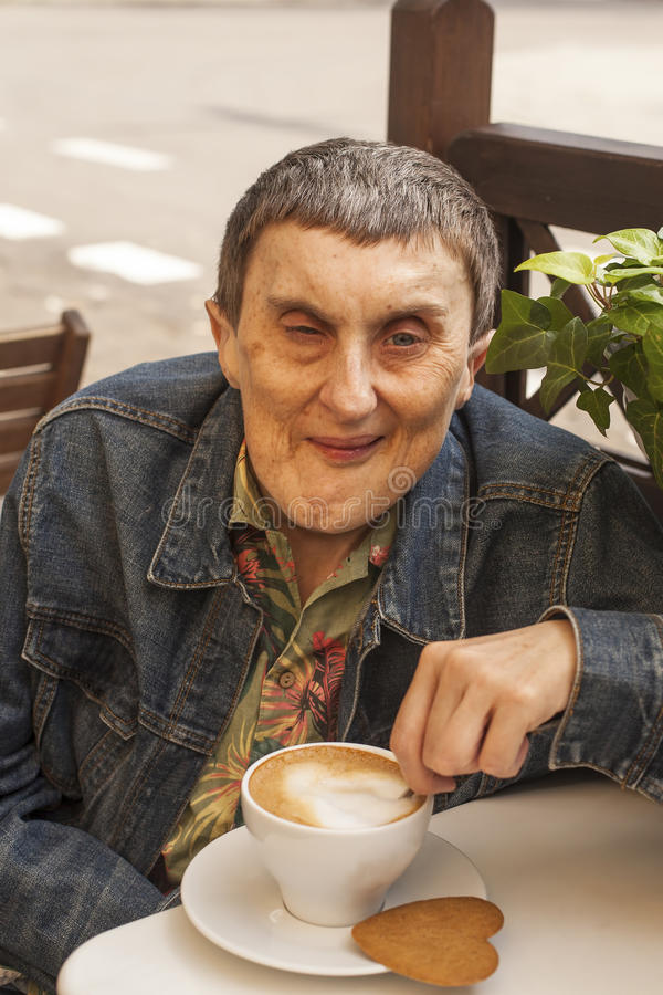 Elderly disabled man with cerebral palsy sitting at outdoor cafe. With cup of coffee royalty free stock images