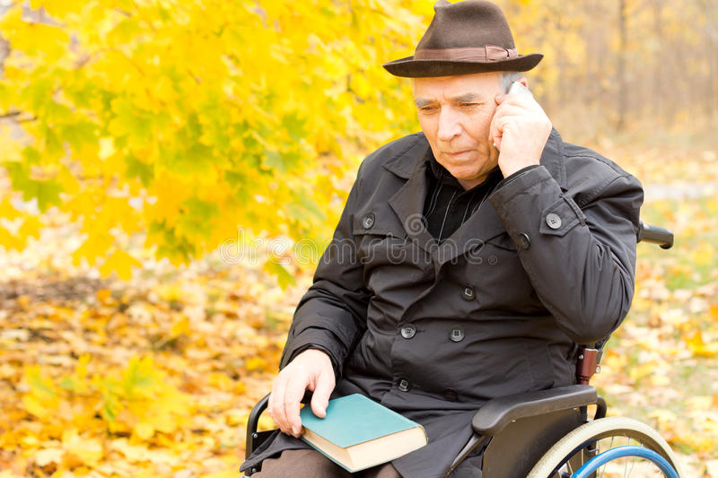 Elderly disabled man using a mobile phone royalty free stock photography