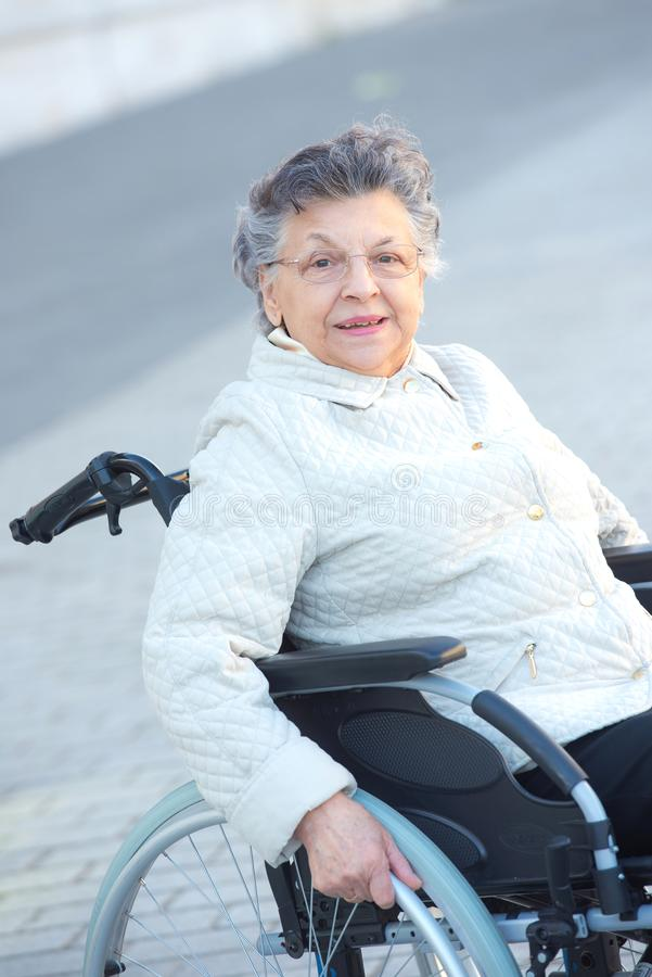 Elderly disabled woman smiling in street. Elderly disabled woman smiling in the street stock images